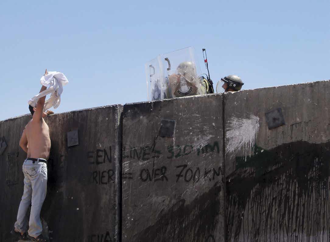 Palestiinalaismies osoittaa mieltään Israelin rakentamaa muuria vastaan Nilinin kylässä Länsirannalla. // Wikimedia Commons