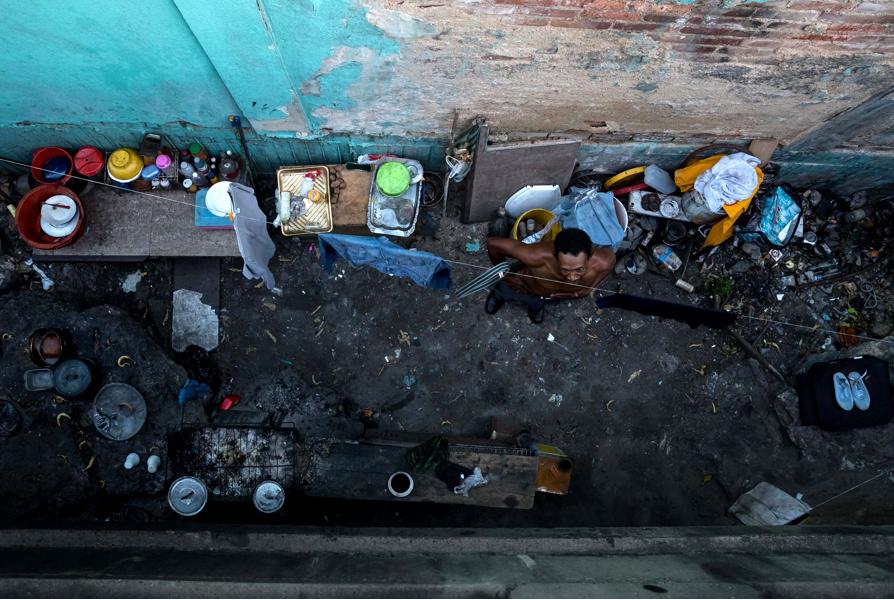 PÄÄKAUPUNKI. Mies kuivatti vaatteitaan Caracasissa joulukuussa. Osa kaupunkilaisista on löytänyt suojaisan majapaikan siltojen alta.