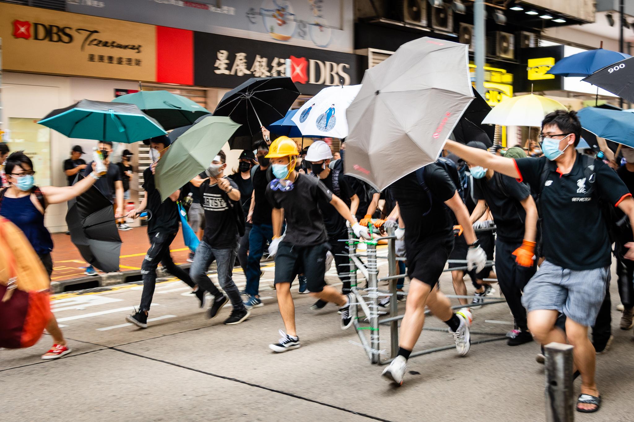 Mielenosoittajat suojautuivat sateenvarjoilla Hongkongin Causeway Bayn alueella heinäkuussa 2019. Kuva: Doctorho/Flickr.
