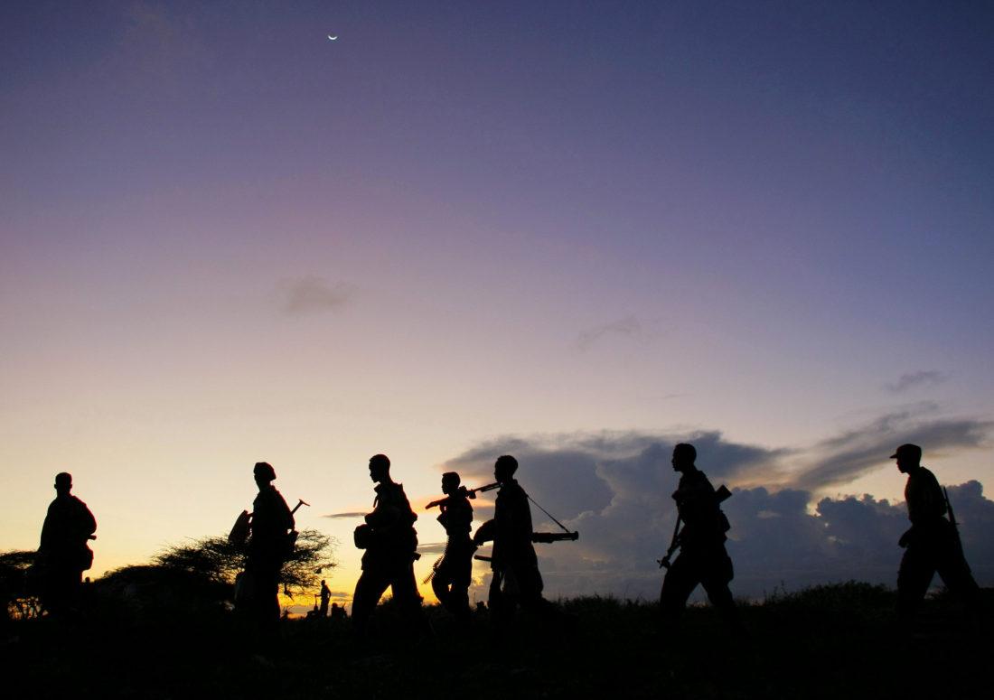 Aseistettuja miehiä auringonlaskua vasten Somaliassa.