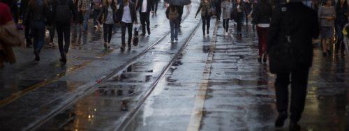 Ihmisiä sateisella kaupungilla.