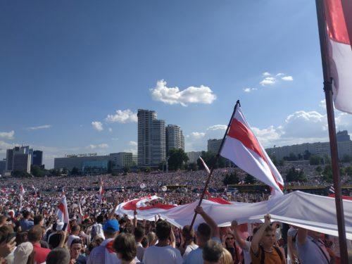 Ihmisiä heiluttamassa punavalkoisia lippuja Minkin kaduilla.
